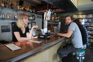 Chelsea Ingram (Bartender) waits for cameras to roll with New York Times bestselling author Jacob Tomsky, playing a background barfly.