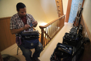 Matt Thomas (sound mixer) sets up in the hallway on location.