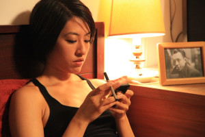 "Photographer character known as ""spanking girl"" (Melody Cheng) checks her phone and vapes in the film Hashtag Annie Hall http://hashtaganniehall.nyc/"