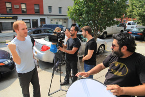 Producer Steve Loff chats with gaffer Walter Fuente as Claudio Rietti and Matt Cutola set up a shot.